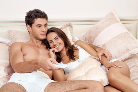 happy-couple-watching-tv-bedroom.jpg450