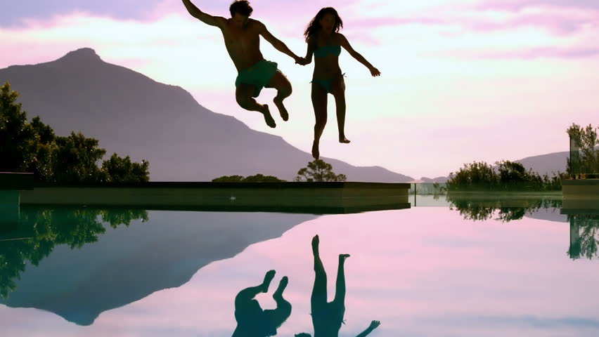 couple jumping over pool